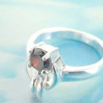 925. stamped silver ring with alien holding a red cz design