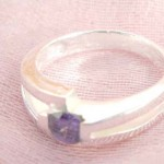 Outstanding 925. stamped silver ring with straight line holding purple crystal design